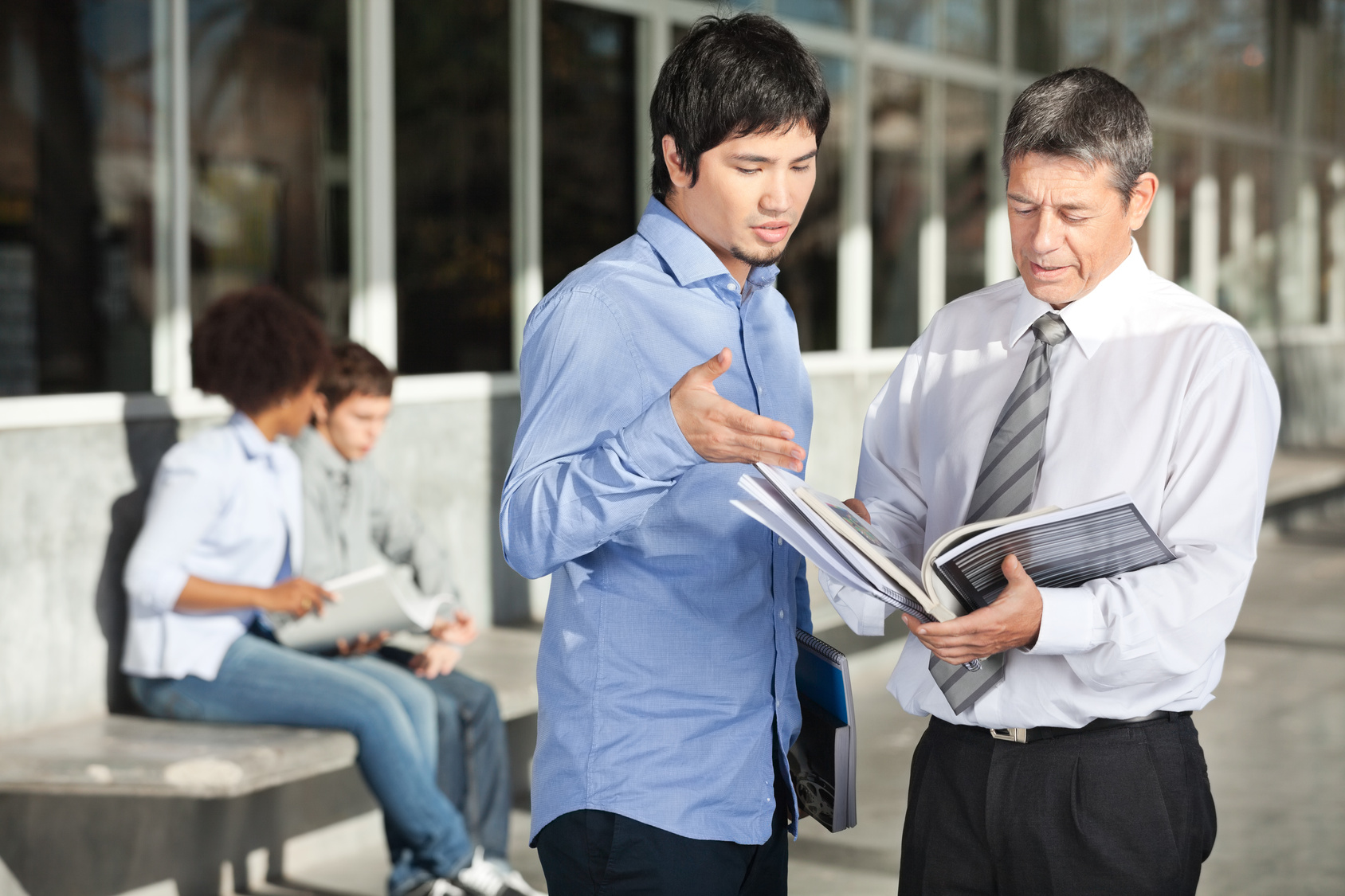 Mature male teacher holding books while discussing with student on college campus